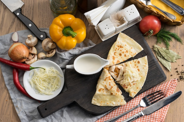 Tortilla with sausages, mozzarella cheese and sour cream on a wooden cutting board