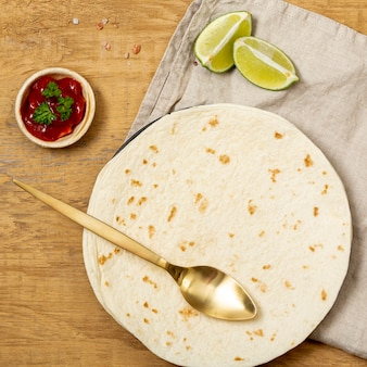 Tortilla with spoon, tomato sauce and sliced lime on table