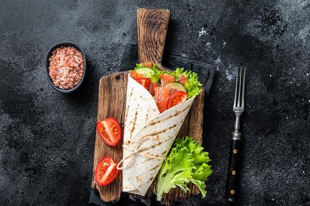 또띠야 연어 롤을 샐러드, 야채로 감싼다. 블랙 테이블. 평면도.