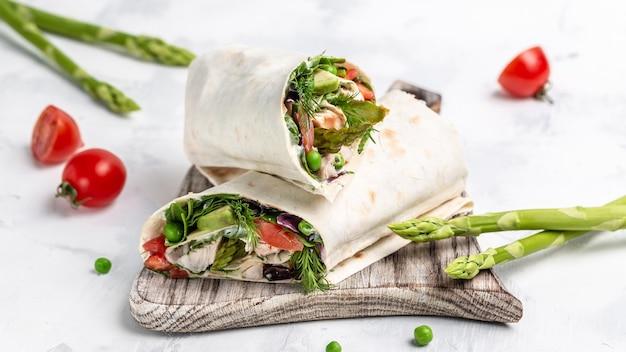 鶏肉と野菜のアスパラガス、アボカド、トマト、エンドウ豆、チーズ、タルタルで包んだトルティーヤ