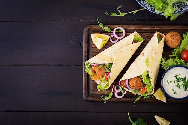 Обертывание из тортильи с фалафелем и свежим салатом. веганские тако. вегетарианская здоровая пища. вид сверху