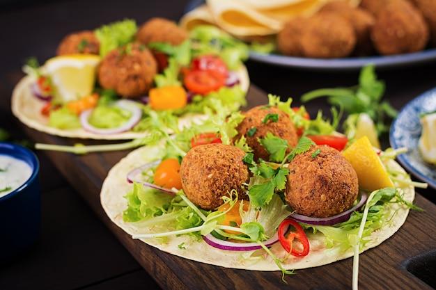 ファラフェルと新鮮なサラダのトルティーヤラップ。ビーガンタコスベジタリアンの健康食品。