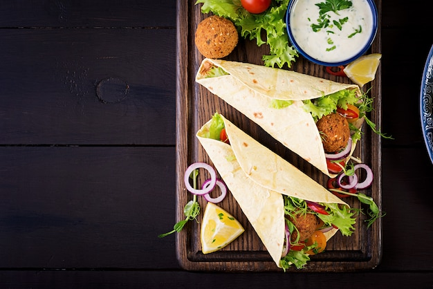 Tortilla wrap with falafel and fresh salad. vegan tacos. vegetarian healthy food. top view