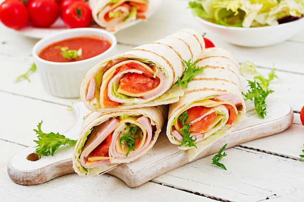 Tortilla wrap with ham, cheese and tomatoes on white wood