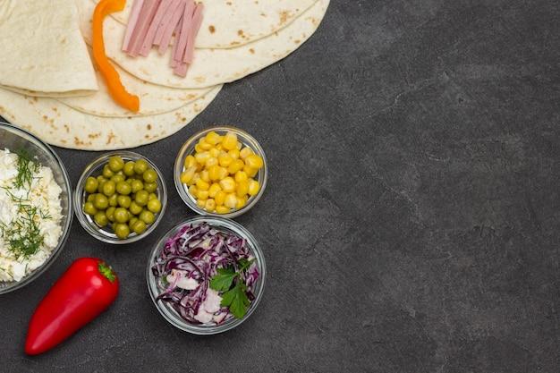 Роллы из тортильи и овощная начинка для тортильи в стеклянных мисках.
