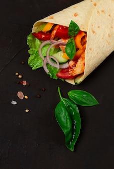 토르티야는 구운 멕시코 치킨을 야채 부리토와 함께 사람이 없는 검은 테이블에 감싼다