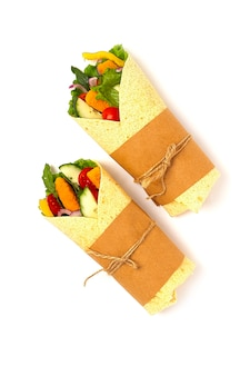 Роллы из тортильи с куриными палочками в панировке с овощами, буррито, на белом фоне, горизонтальные, без людей. фото высокого качества