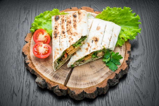 Tortilla wraps with grilled chicken on a wooden background.