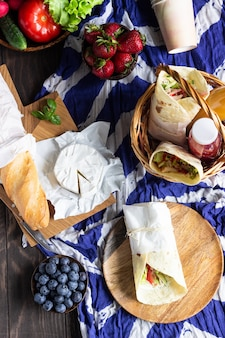 Tortilla wraps with roasted chicken and vegetables, fresh juices, various vegetables and berries, baguette and cheese