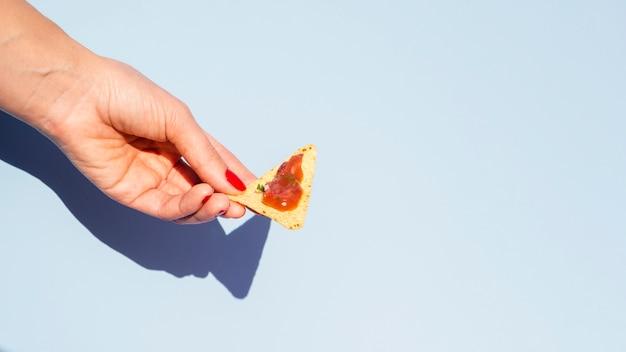 Женщина крупного плана с обломоками tortilla и голубой предпосылкой