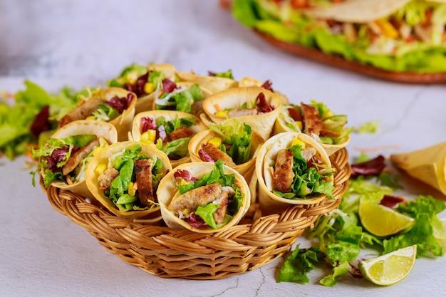 Тортильяс с начинкой из овощей и мяса на корзине с зеленым салатом