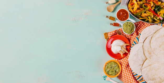 Tortillas and mexican food on tablecloth