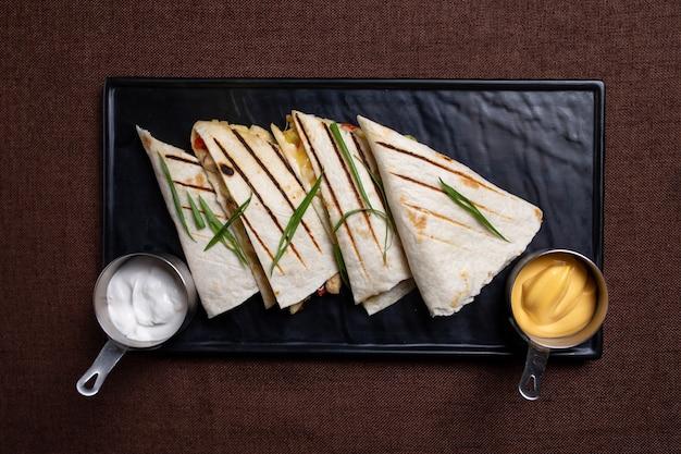 Тортильи с мясной начинкой и соусом на черной тарелке, вид сверху