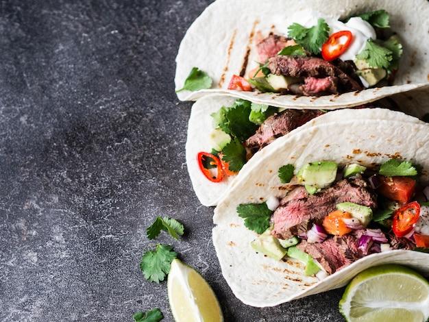 Тортилья с овощами и кусочками говяжьего стейка. авокадо, помидоры, красный лук, а также кинзу и сок лайма в лепешках. мексиканская еда. Premium Фотографии