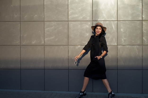 Total look for every day. cheerful young active attractive brunette girl wearing stylish black dress and fashionable hat. model in trendy youth outfit walking on urban wall background.