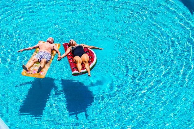 幸せな成熟したシニア退職者のための完全なリラックスは、夏の時間にプールの青い澄んだ水の上に着色されたリロスの膨脹可能なマットレスの上に横たわる