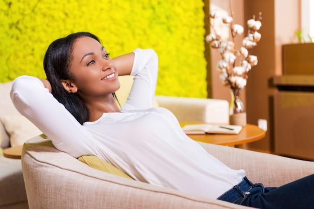 完全なリラクゼーション。頭の後ろで手をつないで笑顔の魅力的な若いアフリカの女性