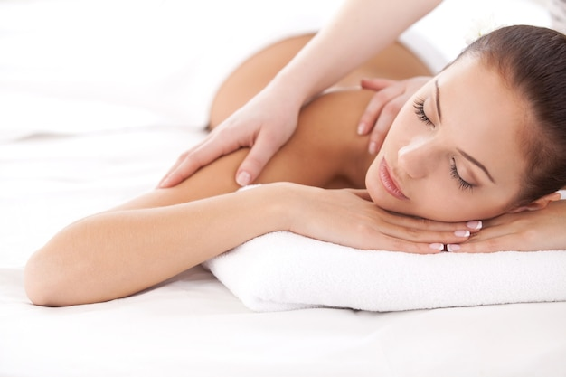 완전한 휴식. 마사지 치료사가 그녀의 어깨를 마사지하는 동안 앞에 누워 카메라를 보고 있는 아름다운 젊은 여성
