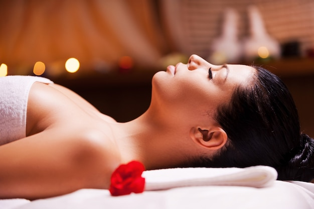 Total relaxation. side view of beautiful young woman wrapped in towel lying on massage table and keeping eyes close