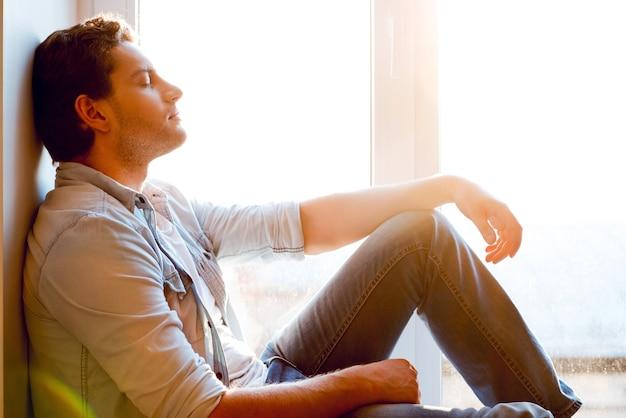 完全なリラクゼーション。窓枠に座って目を閉じているハンサムな若い男の側面図