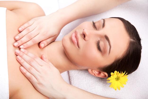 Полное расслабление. вид сверху привлекательной молодой женщины с цветком в голове, лежа и с закрытыми глазами, пока массажист массирует ее