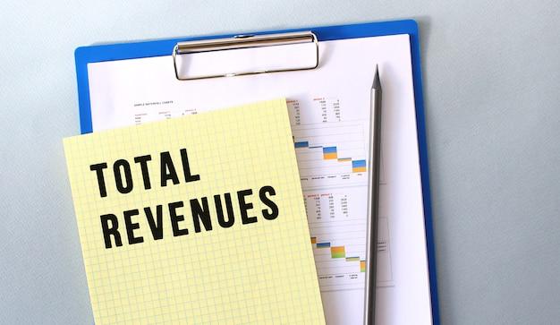 鉛筆でメモ帳に書かれた総収入のテキスト。ダイアグラムのあるフォルダーのメモ帳。財務コンセプト。
