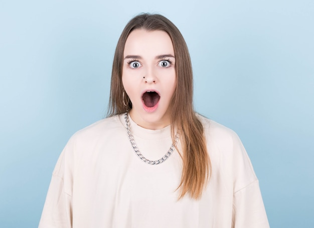 총 판매 및 거대한 할인 개념. 와우, 큰 눈을 가진 wtf 얼굴 여자의 초상화를 닫고 입을 벌리고 파란색 배경에 고립 된 현대 머리