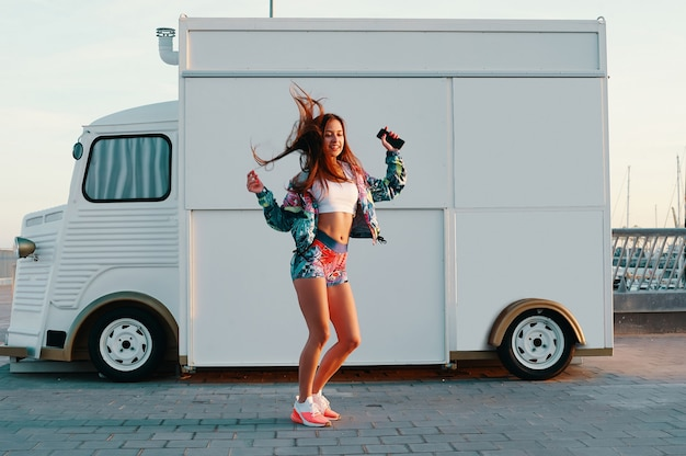 Совершенно беззаботно. полная длина привлекательной молодой женщины в спортивной одежде танцует и улыбается, стоя против грузовика с едой на открытом воздухе
