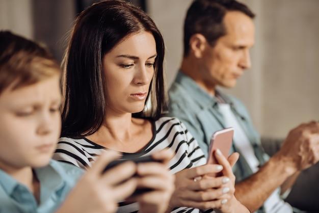 Полностью концентрированный. приятная молодая женщина использует свой телефон и сосредоточена на нем, сидя между мужем и сыном, играя в игры