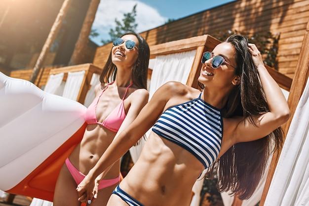 여름날을 즐기는 수영복과 선글라스를 입은 완전히 자유롭고 행복한 두 명의 귀여운 젊은 여성