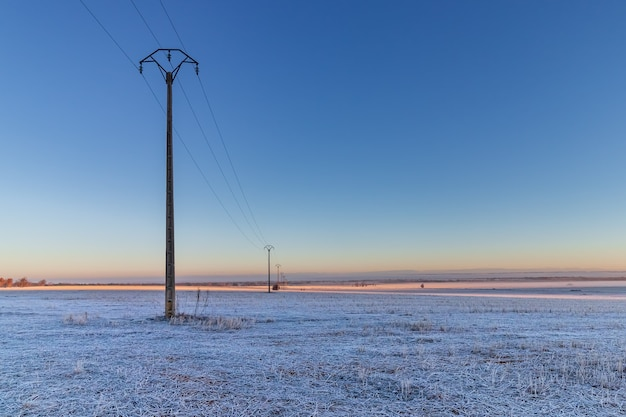 Totally frozen winter landscape in shades of blue and with electric poles in perspective. spain.