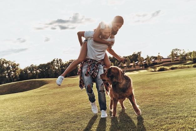完全に恋をしています。屋外で犬と一緒に歩いている間、肩に若い魅力的な女性を運ぶハンサムな若い男の全長