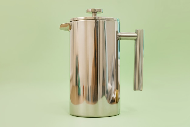 Totally made from stainless steel frenchpress stays on a light green background.