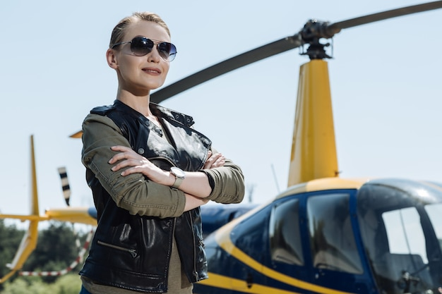 Totally ready. pretty young female pilot folding her arms across her chest and posing for the camera before taking a helicopter ride