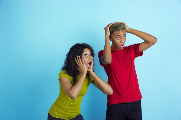 Totally shocked look at side like sport fans. young emotional african-american man and woman in colorful clothes on blue background.