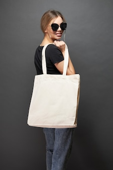 Эко-сумка для макета держит женщина над серой текстурой