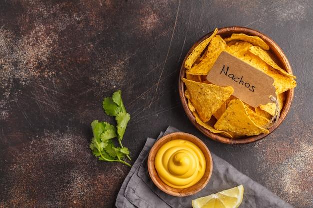 メキシコ料理のコンセプトです。ナチョス - 木製ボウル、上面図、コピースペースのチーズソース添え黄色トウモロコシtotoposチップ。
