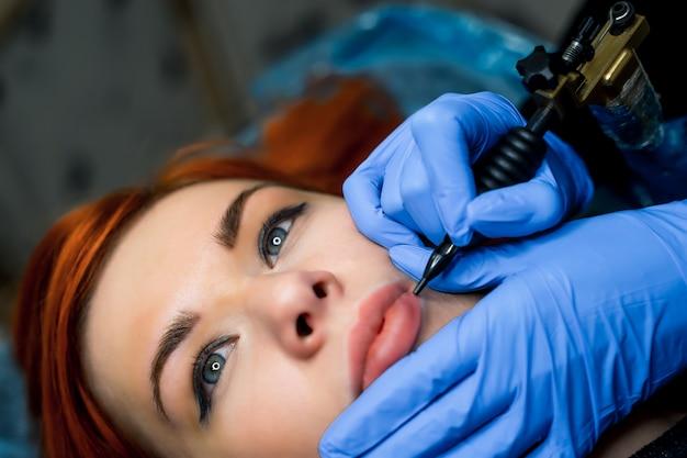 Красивое лицо женщины и руки косметолога, делать tototo на губах.