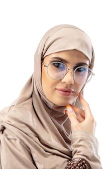接する。広告のためのコピースペースでスタジオの背景に分離されたスタイリッシュなヒジャーブでアラブの女性を閉じます。ファッション、美容、スタイルのコンセプト。トレンディなメイク、マニキュア、アクセサリーを備えた女性モデル。