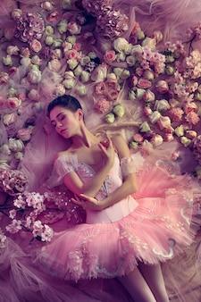 일몰의 터치. 꽃으로 둘러싸인 핑크 발레 투투에서 아름 다운 젊은 여자의 최고 볼 수 있습니다. 산호 빛의 봄 분위기와 부드러움. 봄, 꽃, 자연의 각성 개념.