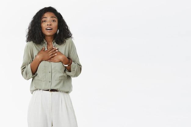 Умиленная и восхищенная юная робкая темнокожая подружка с кудрявой прической и модным нарядом держит ладони на груди и вздыхает от ласки