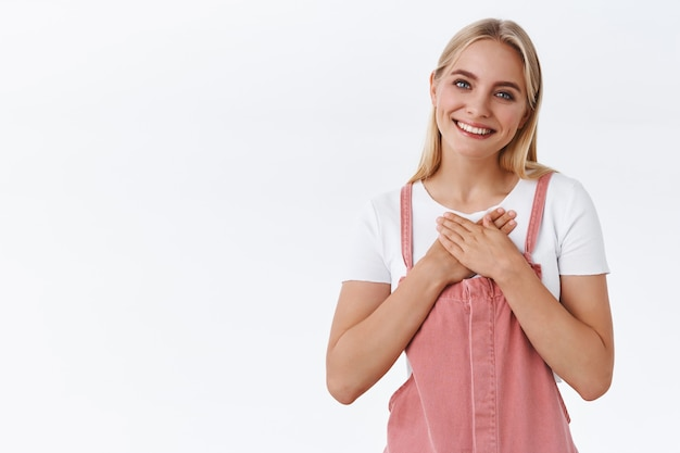 Прикосновенная белокурая девчонка чувствует благодарность, сердечные искренние согревающие поздравления, прижимает ладони к сердцу, наклоняет голову и радостно улыбается, горячо благодарит за подарки, белый фон