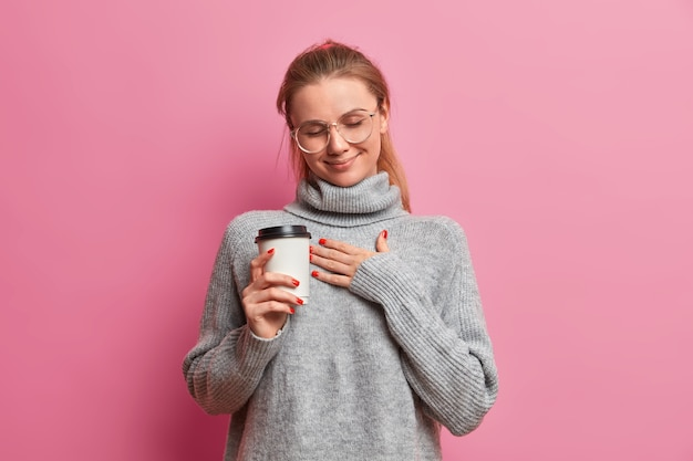 Touched european woman presses hand to chest, holds takeaway coffee, dressed in oversized jumper, recalls something pleasant