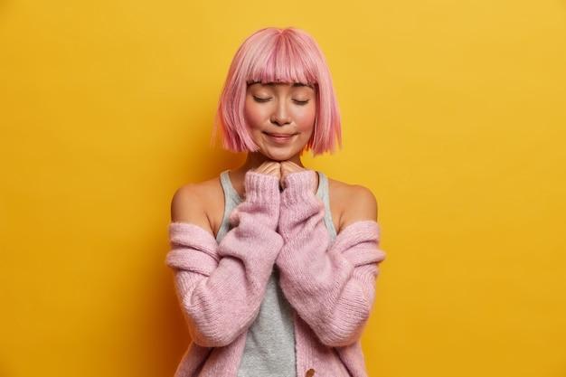 触れられた素敵な女性はピンクのボブの髪型とフリンジを持ち、屋内に立って目を閉じ、手をあごの下に保ちます