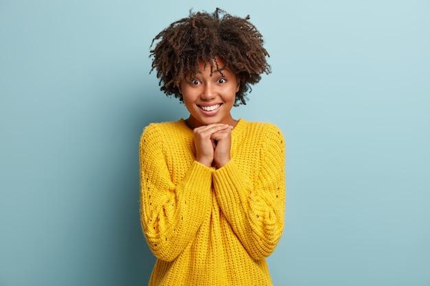 La donna afroamericana commossa e soddisfatta tiene le mani unite sotto il mento, prova ammirazione, esprime emozioni positive, ha un sorriso a trentadue denti, indossa un maglione giallo, si diverte e ride al chiuso. concetto di emozioni