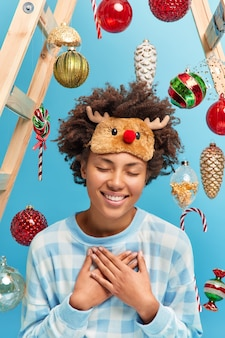 Touched pleased dark skinned woman spends holidays time at home makes gratitude gesture closes eyes with pleasure wears comfortable casual clothes busy decorating house for new year or christmas