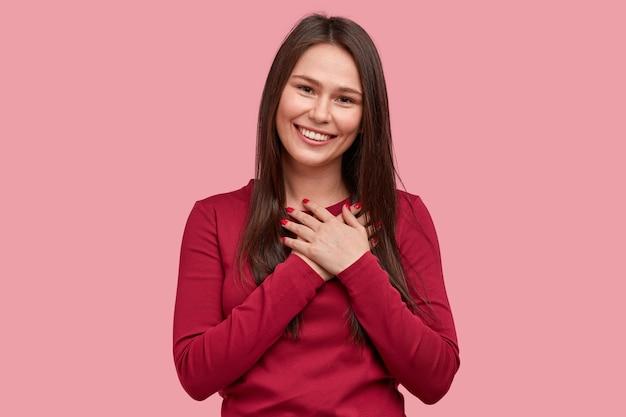Прикосновенная позитивная женщина с довольным выражением лица держит руки на груди, чувствует благодарность, впечатленная добрыми словами благодарности, изолированными на розовом фоне. люди