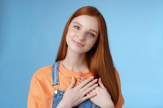 触れられたロマンチックな優しいかわいい赤毛フェミニンな女の子青い目傾斜頭溶ける心温まるジェスチャーは喜んで楽しいperstタッチハート笑顔感謝感ロマンス愛青い背景を受け取ります