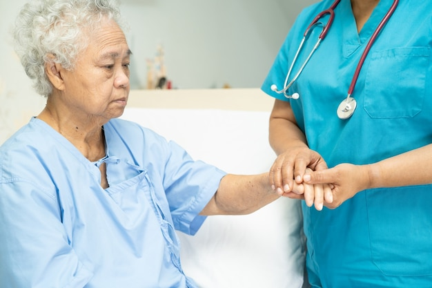 Touching asian senior woman patient with love care helping encourage and empathy at hospital