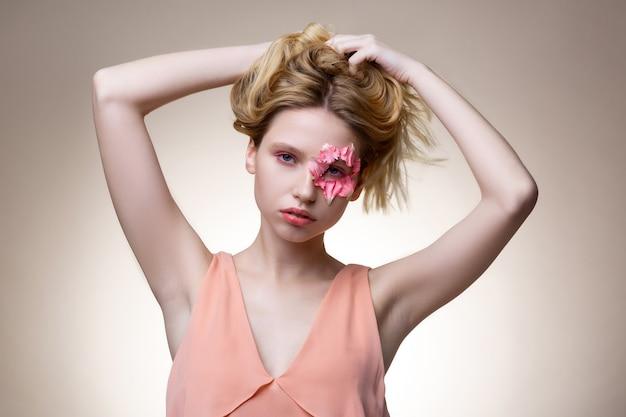 髪に触れる。彼女の金髪のウェーブのかかった髪に触れている目の周りの花びらを持つ青い目のモデル